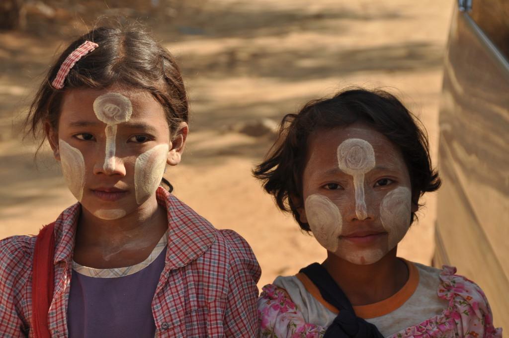 Reisebild von Myanmar in Asien. Zwei junge burmesische Mädchen tragen die traditionellen Gesichsbemalung aus Baumrinde, auch Thanaka genannt.