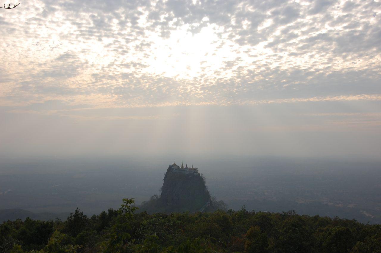 Reise in Myanmar in Asien. Stimmungsbild mit der Erhebung Mount Popa, dessen Kloster von der Sonne beschienen wird.