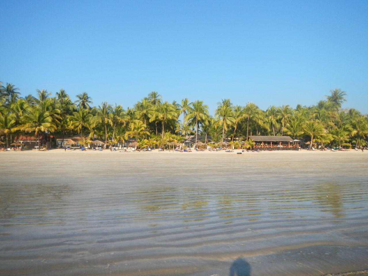 Reise in Myanmar in Asien. Sicht vom Meer aus an den Sandstrand von Ngapali mit vereinzelten Liegestühlen und Strandlokalen