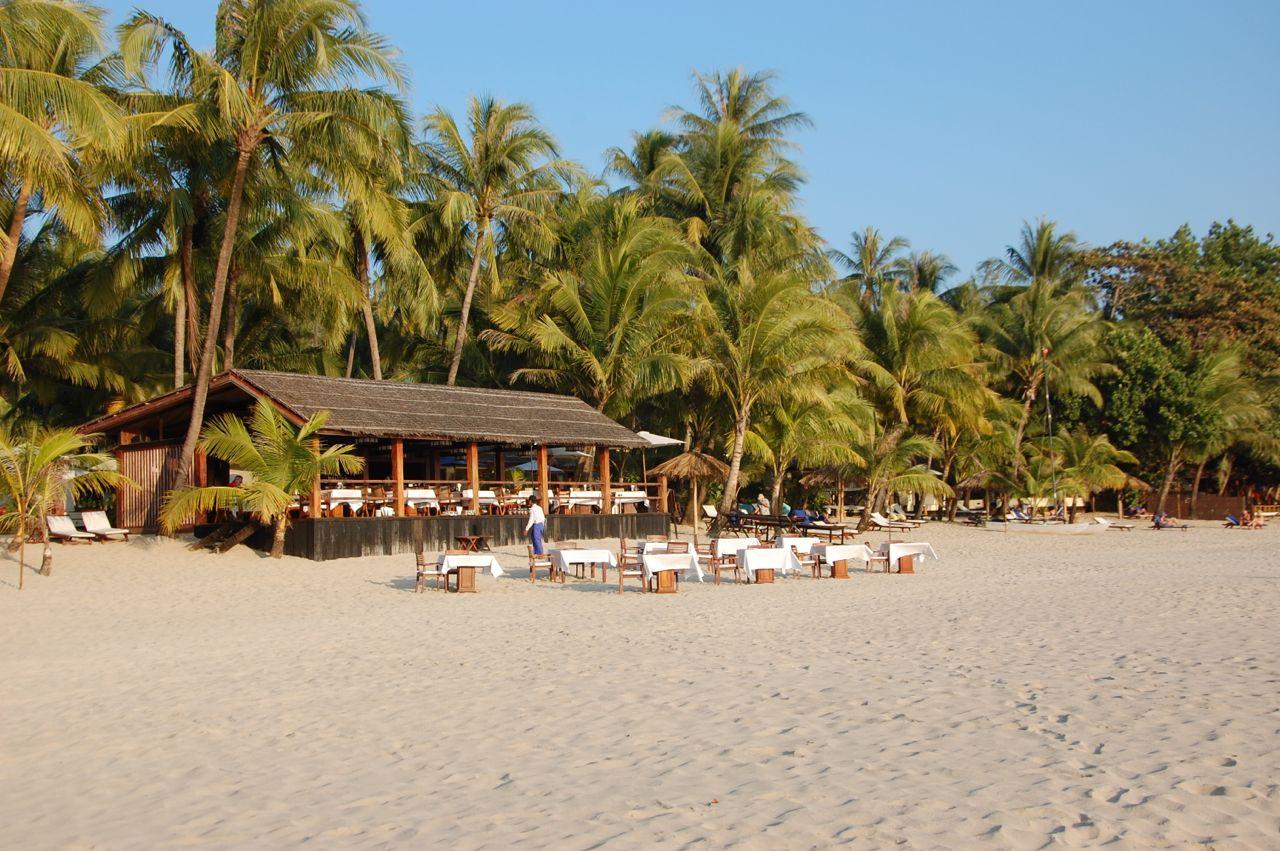 Reise in Myanmar in Asien. Am Strand von Ngapali ist ein Restaurant mit Tischen im Sand zu sehen, mit Palmen im Hintergrund