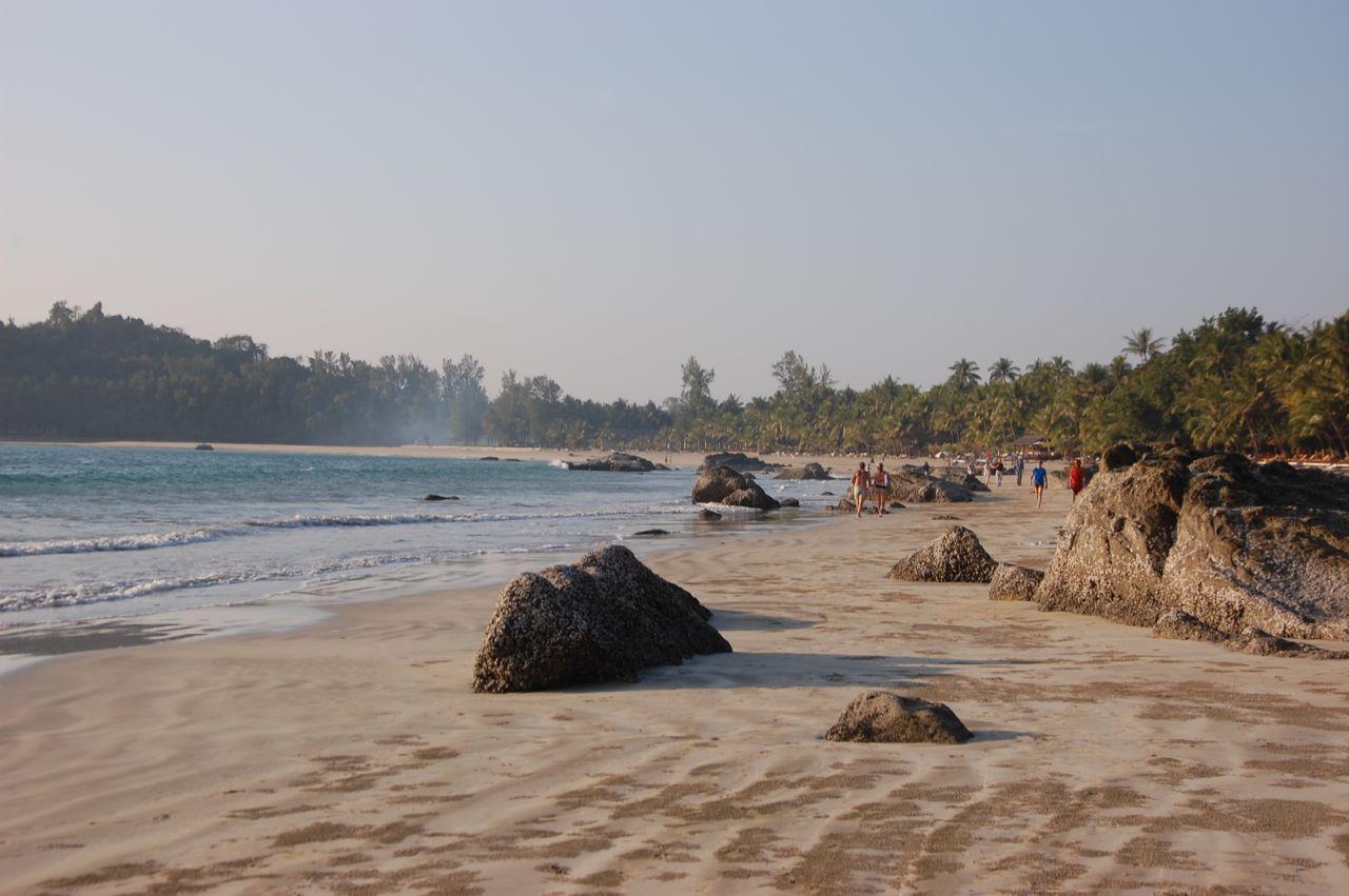 Reise in Myanmar in Asien. Bei Ebbe spazieren ein paar Menschen den weiten Strand von Ngapali entlang.