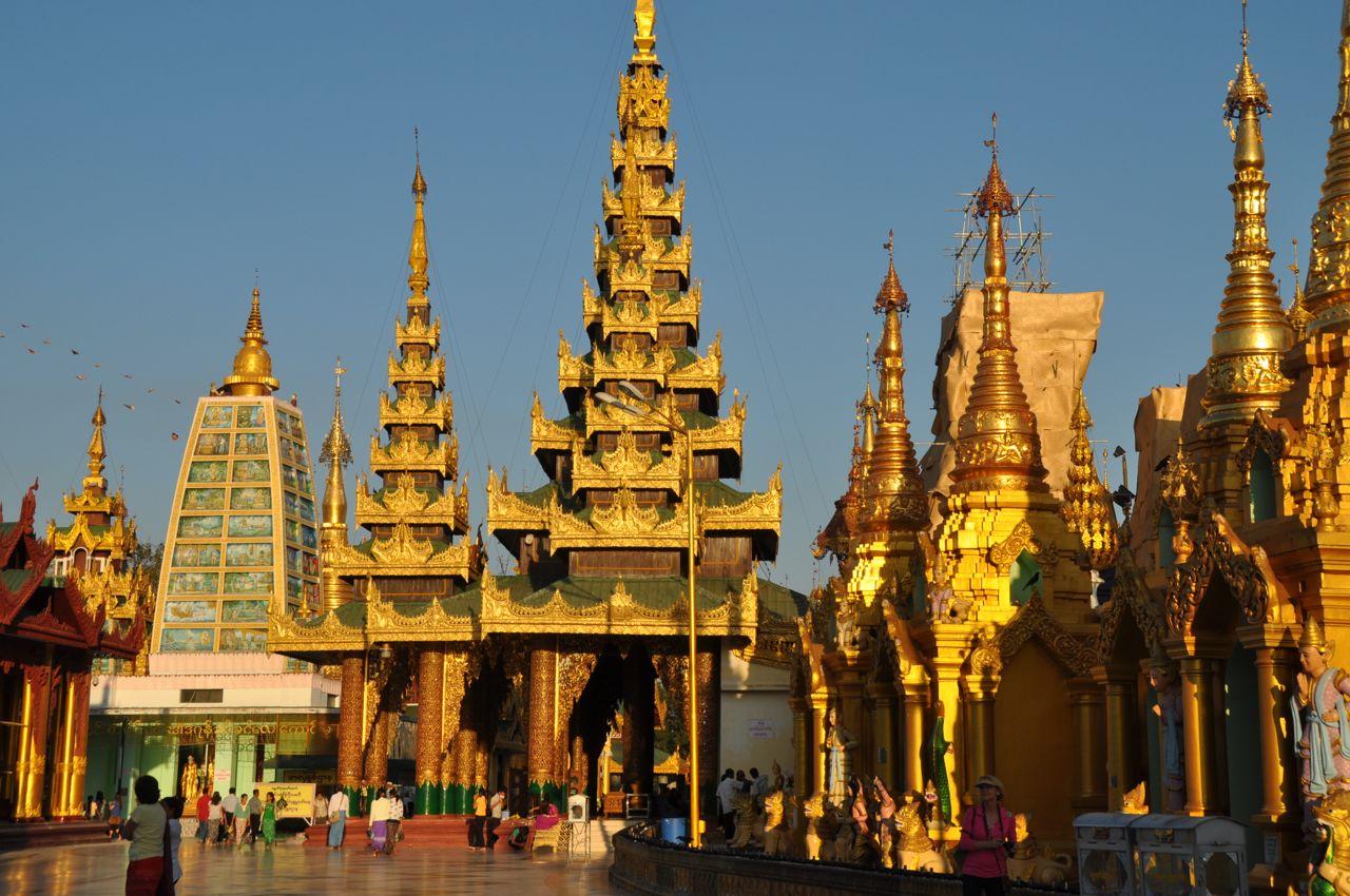 Reise in Myanmar in Asien. Die goldenen Dächer und die zahlreichen Besucher der weitläufigen Tempelanlage bei der Shwedagon Pagode in der burmesischen Stadt Yangon werden von der Abendsonne beschienen.