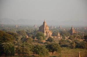 Reise in Myanmar in Asien. Stimmungsbild mit Aussicht auf zahlreiche Tempel in der historischen Königsstadt Bagan, von üppiger Natur umgeben.