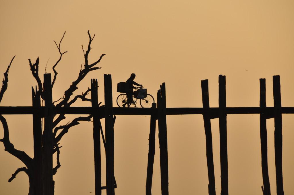 Reise in Myanmar in Asien. Stimmungsbild mit einheimischem Mann, schiebt auf U-Bein Brücke ein vollbeladenes Fahrrad in Abenddämmerung