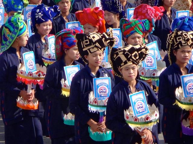 Reise in Myanmar in Asien. Burmesische Frauen in traditioneller Kleidung und mit typisch burmesischer Kopfbedeckung nehmen an der Prozession des burmesischen Nationalfeiertags PaO in der Stadt Taunggyi teil.