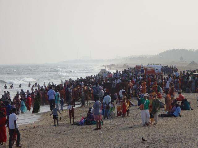Reise in Indien in Asien. An einem Strand hat sich eine Menschenmenge versammelt, manche Menschen baden im Meer in der Abenddämmerung.