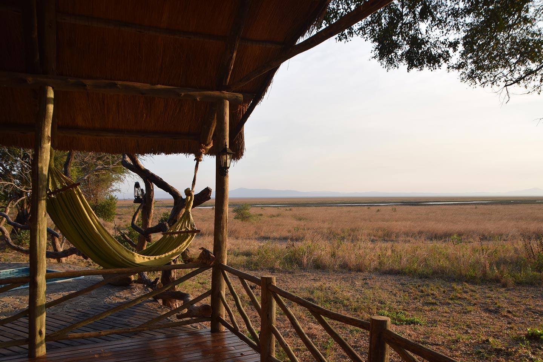 Reise in Tansania in Afrika. Aus einem Bungalow mit Hängematte sieht man auf die weite Savanne.