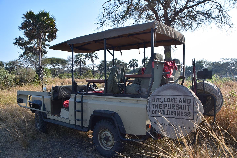 Reise in Tansania in Afrika. Safari Jeep von Nomad Tansania mit sechs Sitzplätzen steht in der Savanne.