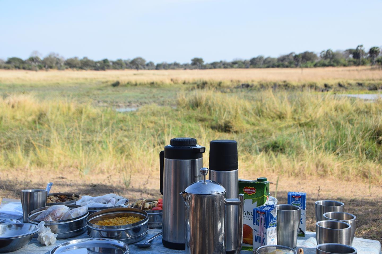 Reise in Tansania in Afrika. Mitten in Savanne steht ein reich gedeckter Frühstückstisch für die Verpflegung nach einer Safari.