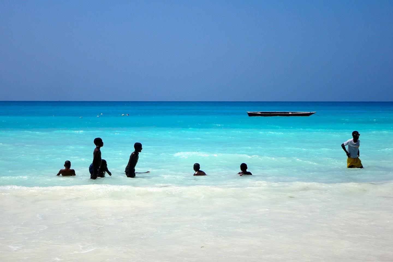 Reise in Sansibar in Afrika. Im türkisfarbenen Meer baden sieben einheimische Kinder, im Hintergrund schaukelt ein verlassenes Fischerboot
