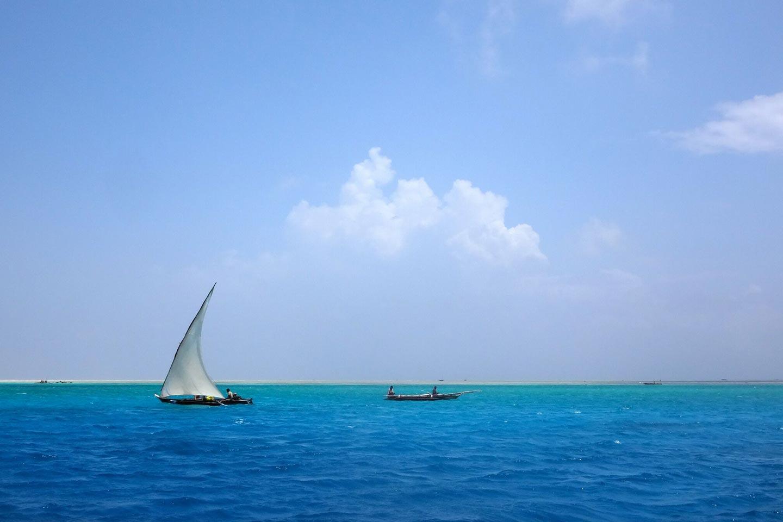 Reise in Sansibar in Afrika. Auf türkisblauen Meer schaukeln vereinzelte Fischerboote.