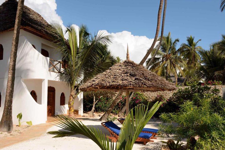 Reise in Sansibar in Afrika.Vor einem Zimmer der in traditionellem Stil gehaltenen Hodi Hodi Pension stehen unter üppigen Palmen zwei Liegestühle.