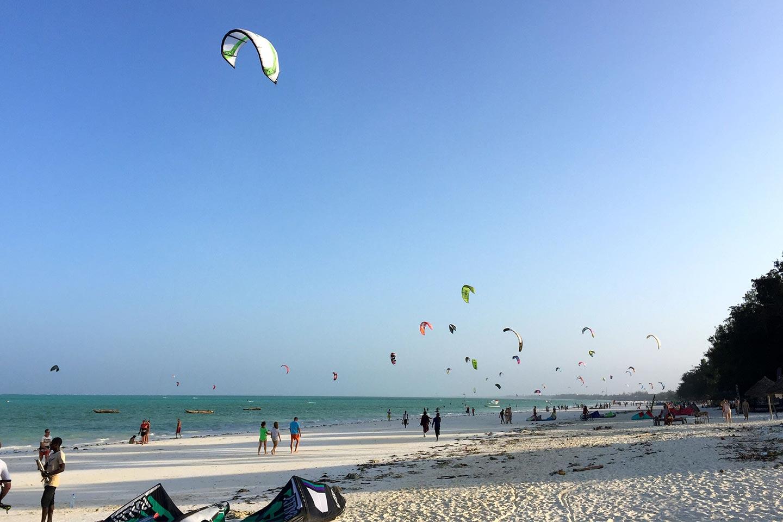 Reise in Sansibar in Afrika. Einige Spaziergänger laufen über langen Sandstrand, der Himmel ist bedeckt mit den Segeln von zahlreichen Kitesurfern.