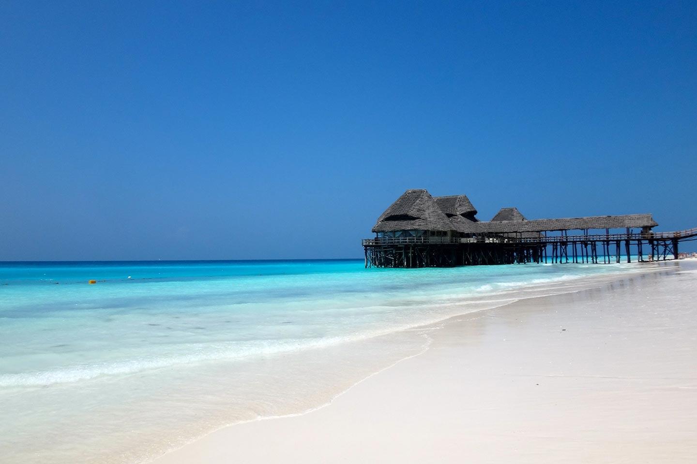 Reise in Sansibar in Afrika. Sicht über langen weissen Sandstrand, ein grosser Stelzenbungalow steht im türkisfarbenen Meer.