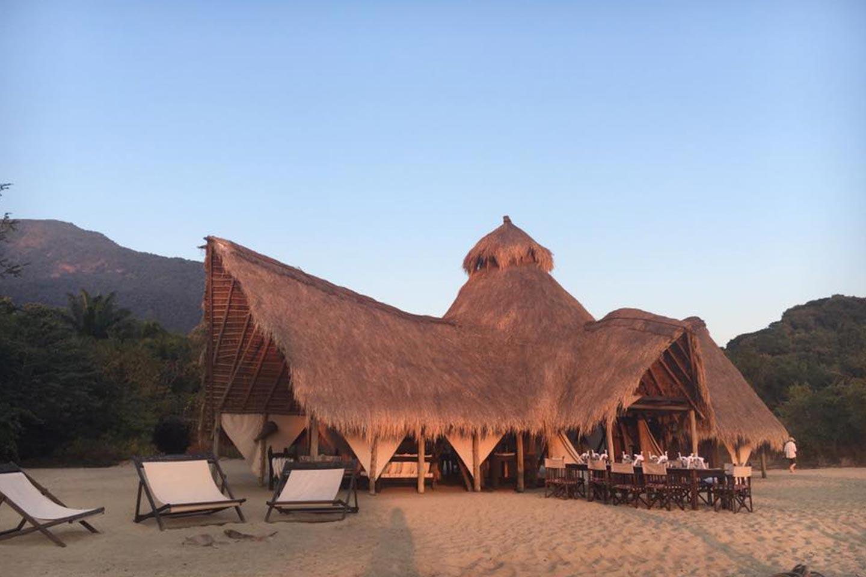 Reise in Tansania in Afrika. Mitten in der Natur steht das Greystoke Camp im Mahale Nationalpark, die Tische des Restaurants stehen direkt im Sand.
