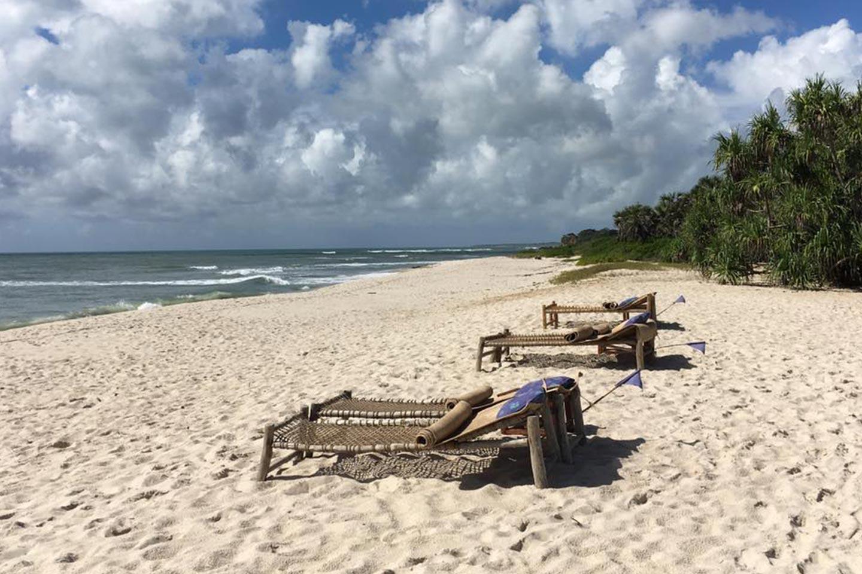 Reise in Tansania in Afrika. Sandstrand mit zwei einfachen Liegestühlen, im Hintergrund brechen sich die Wellen vom Meer.
