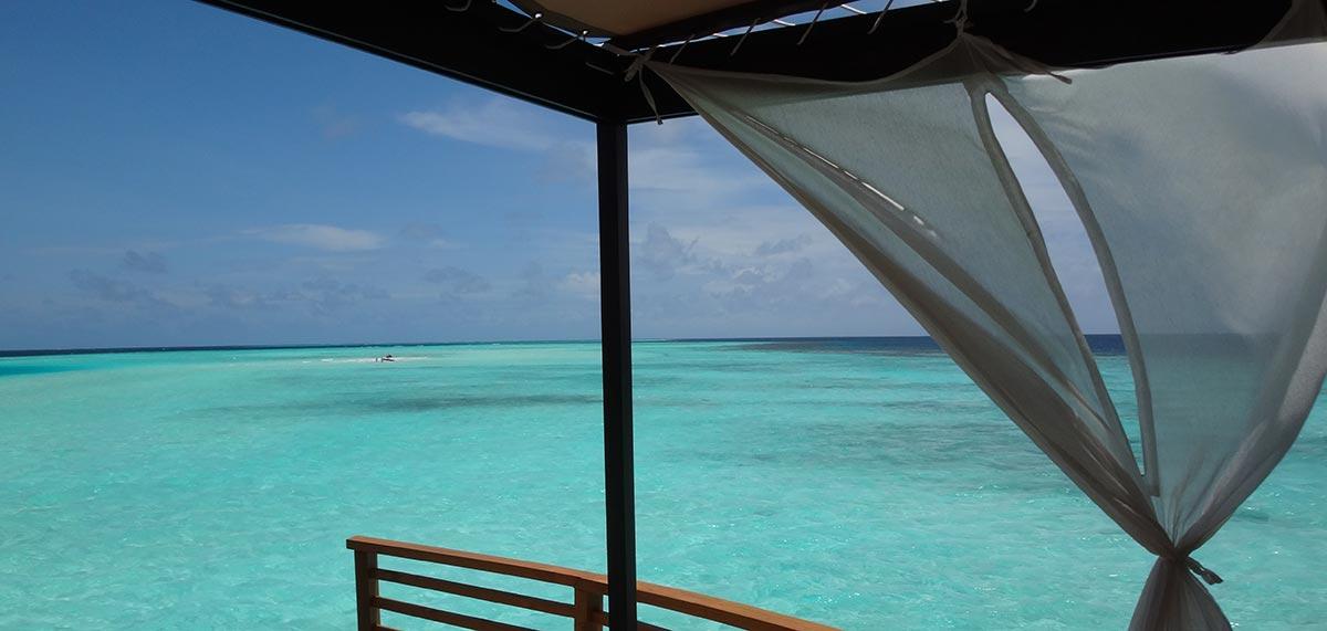 Reise in die Malediven in Asien. Aussicht von Wasserbungalow auf der Insel Baros aus auf das türkisfarbene Meer, weisse Vorhänge bauschen sich im Wind.