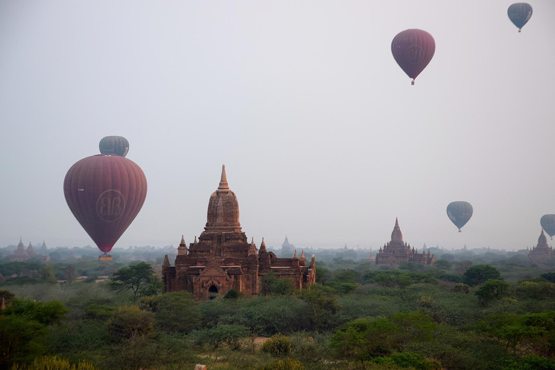 Reise in Myanmar in Asien. Über der Tempellandschaft in Bagan schweben sechs Heissluftballons