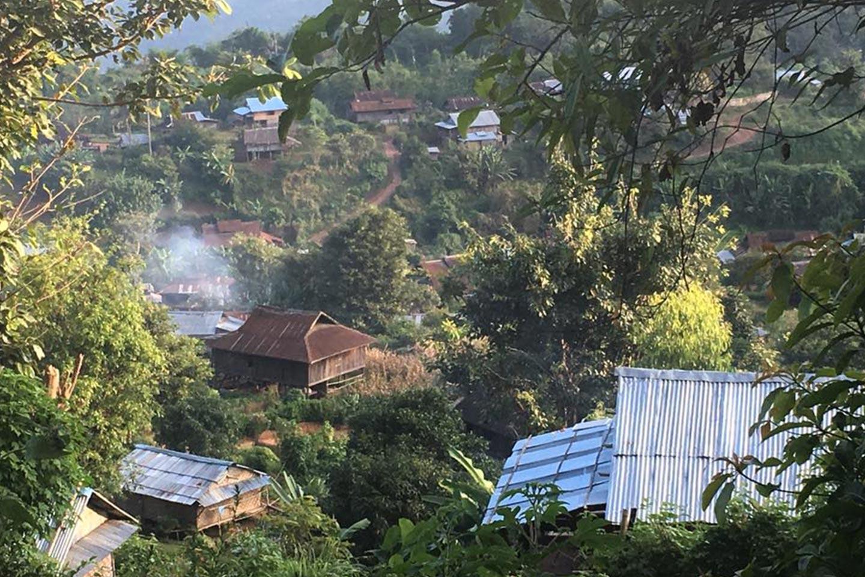 Reise in Myanmar in Asien. In einem Dorf in den Bergen stehen vereinzelt einfache Hütten und Behausungen, umgeben von üppigem Urwald.