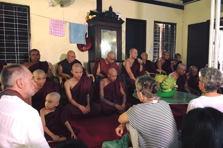 Reise in Myanmar in Asien. Kleingruppe sitzt zusammen mit einigen buddhistischen Mönchen in Raum und meditiert.