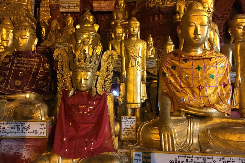 Reise in Myanmar in Asien. Goldene, reich verzierte Buddhastatuen in unterschiedlichen Grössen stehen nebeneinander aufgereiht.