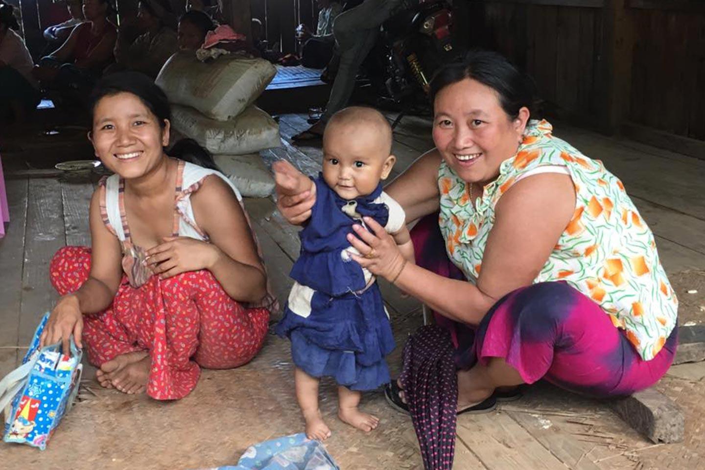 Reise in Myanmar in Asien. Zwei einheimische Frauen spielen mit einem Kleinkind auf dem Boden in ihrem Zuhause.
