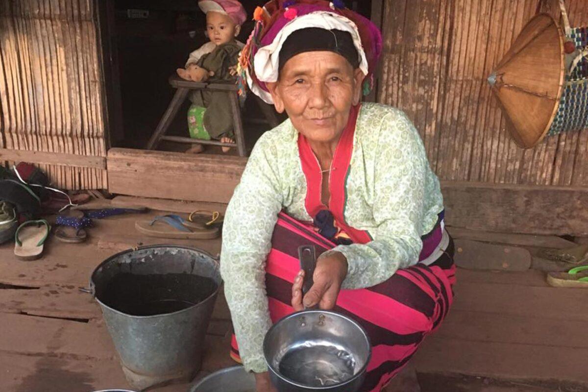 Reise in Myanmar in Asien. Eine ältere, burmesische Frau in traditoneller Kleidung hantiert vor ihrem Haus mit Pfannen und Kochtöpfen. Im Hintergrund sitzt ein kleiner Junge in einem Kinderstuhl.
