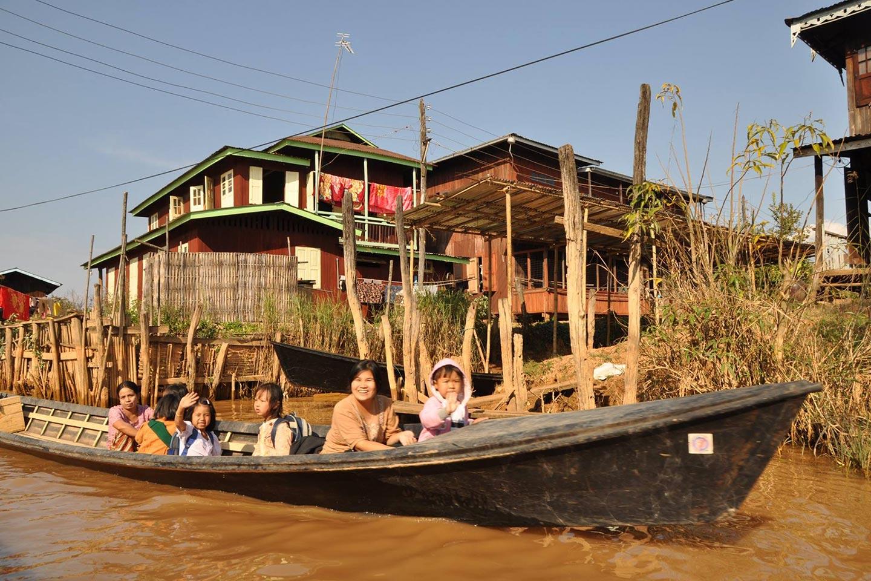 Reise in Myanmar in Asien. Auf einem für die Region des Inle See typischem Langboot fahren zwei einheimische Familien mit Kindern und winken in die Kamera, im Hintergrund ist ein Dorf auf Stelzen zu sehen.
