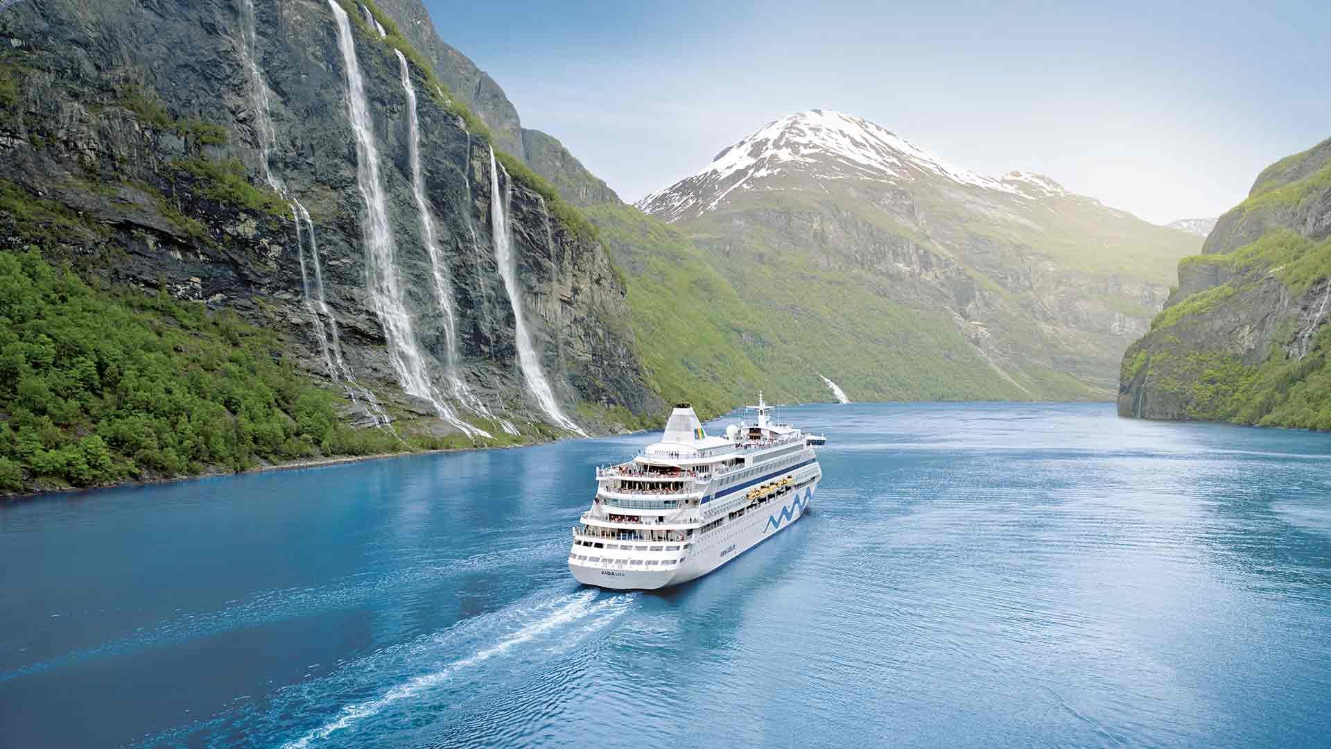 Aida Selection Kreuzfahrt Expedition in Norwegen. Das Aida Kreuzfahrtschiff fährt in ein norwegisches Fjord ein, hohe Wasserfälle stürzen ins Meer, die Berghänge sind von Wäldern und Schnee bedeckt.