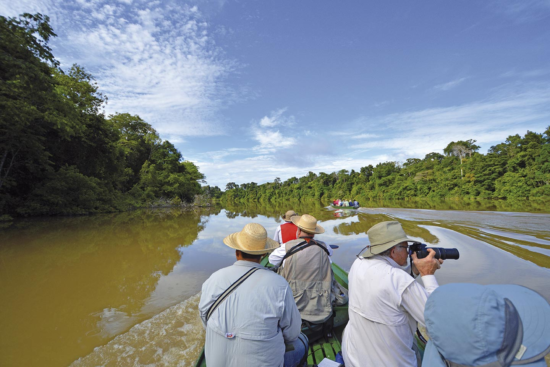 Reise in Amazonas in Südamerika. Zwei kleine Ausflugsboote unternehmen mit Touristen eine Fahrt auf dem Fluss, einige Passagiere halten Kameras in den Händen, der Wald wird auf der glatten Oberfläche des Flusses gespiegelt.