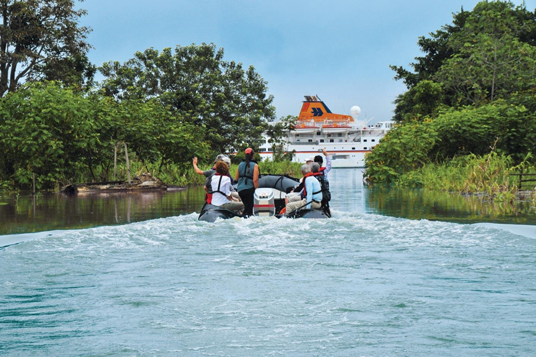 Reise in Amazonas in Südamerika. Auf einem motorisierten Schlauchboot fährt eine kleine Reisegruppe auf dem Fluss ihrem Kreuzfahrtschiff von der Reederei Hapag Lloyd entgegen.