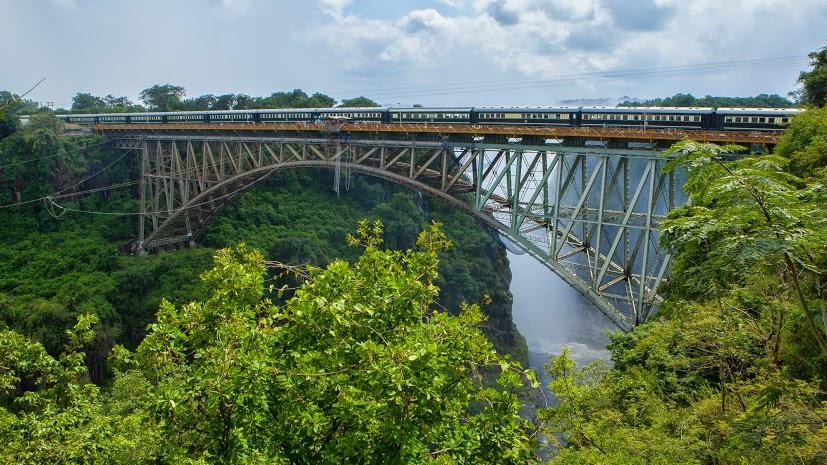 Zugreise mit Rovos Rail in Afrika. Die Bahngeleise führen über eine Brücke, im Hintergrund sind die Viktoriafälle zu sehen