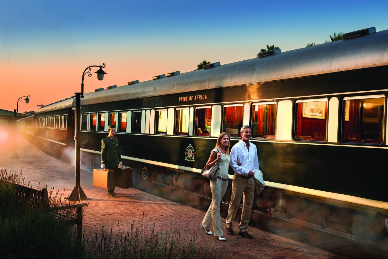 Zugreise mit Rovos Rail in Afrika. Vor dem Zug läuft ein junges Paar auf dem Bahnsteig, dahinter trägt ein Angestellter in Livree die Koffer.