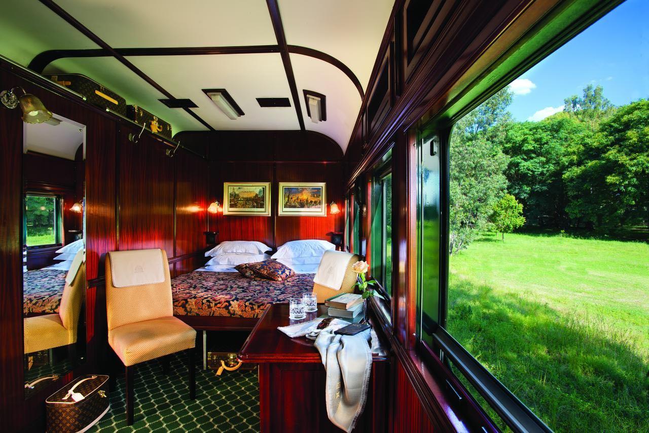 Zugreise mit Rovos Rail in Afrika. Grosszügige Schlafkabine mit Doppelbett, Sitzgelegenheiten und Schreibtisch. Am Fenster zieht in üppigen Grün Natur vorbei.
