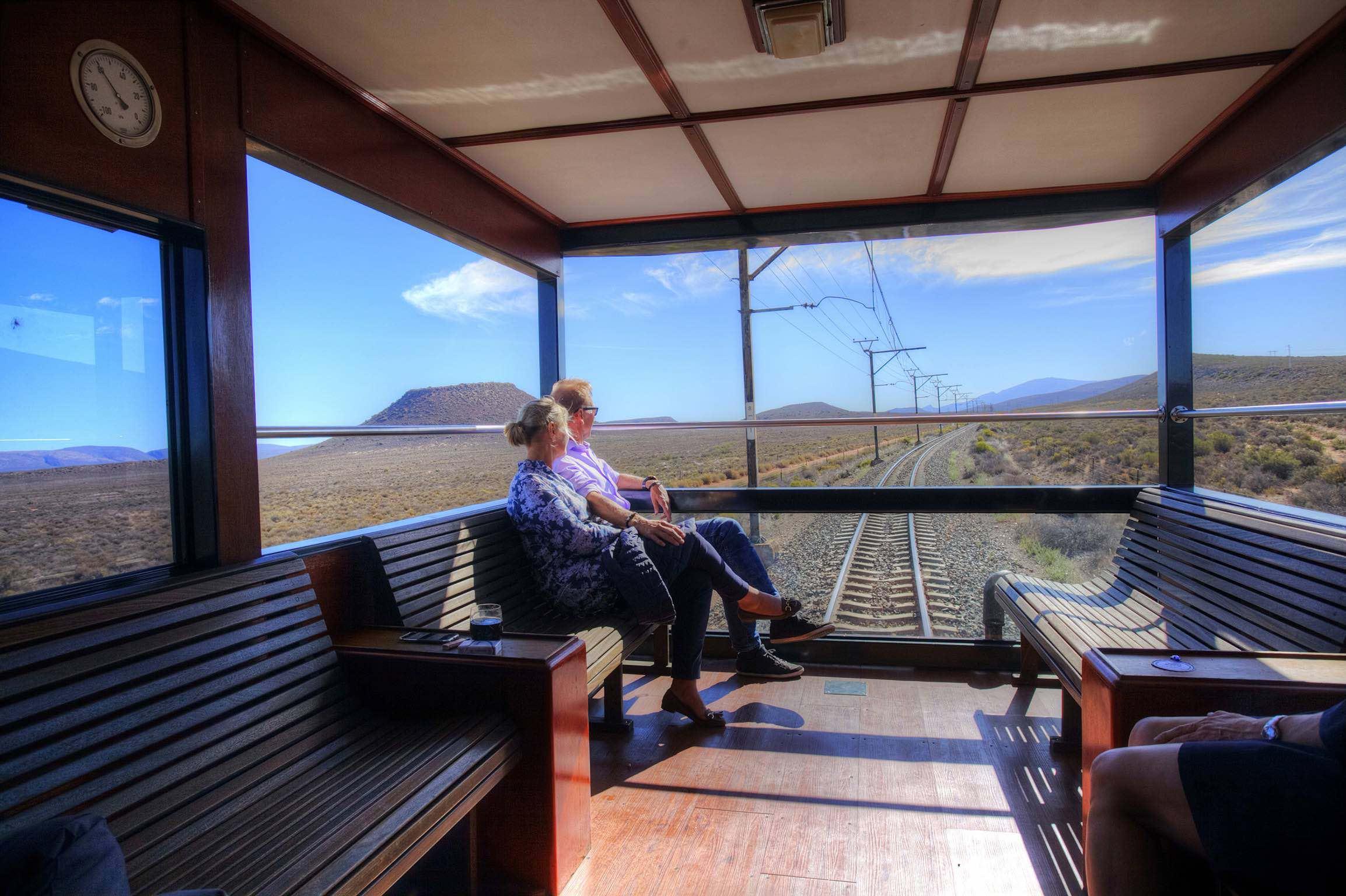 Zugreise mit Rovos Rail in Afrika. Geräumige Lounge mit Holzbänken und grossen Fenstern im letzten Waggon, ein älteres Paar geniesst die Aussicht.