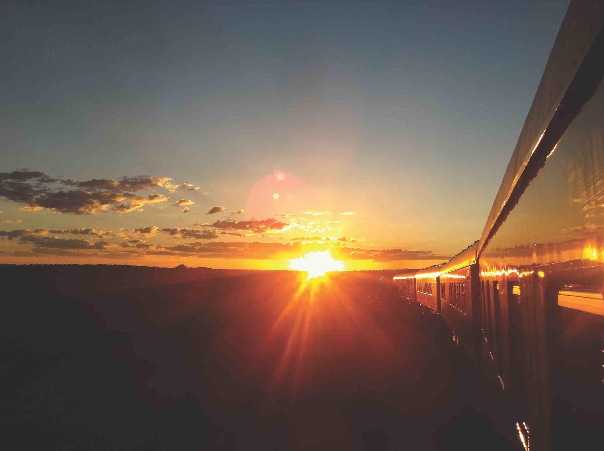 Zugreise mit Rovos Rail in Afrika. Während der Fahrt Fotografie aus einem Abteil, der Zug wird von der untergehenden Sonne beleuchtet.
