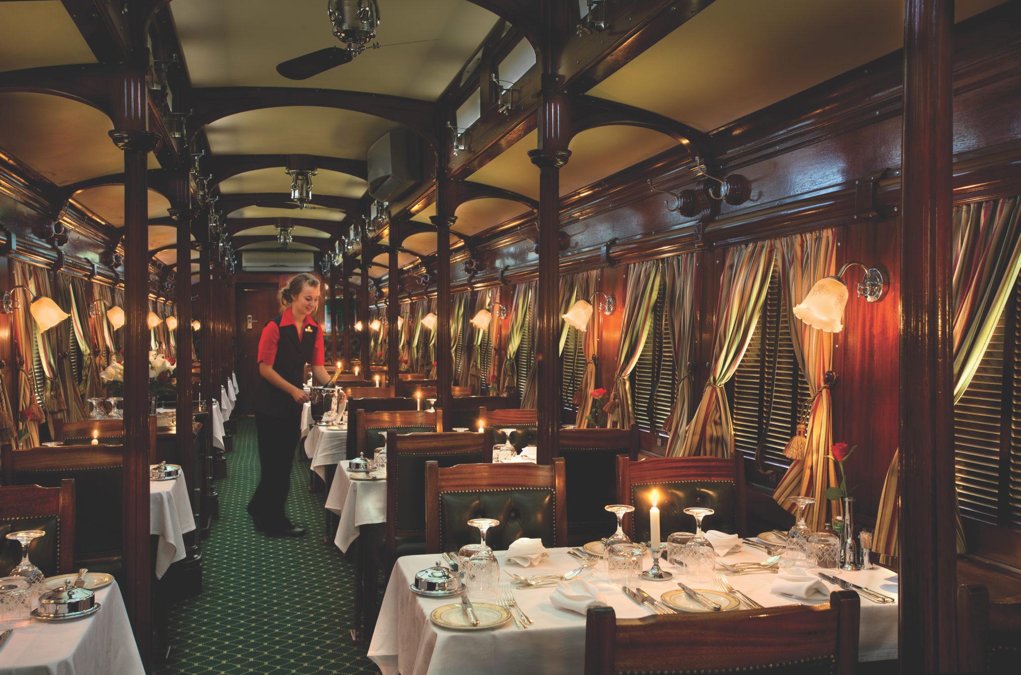 Zugreise mit Rovos Rail in Afrika. Speisewagen mit gedeckten Tischen und Einrichtung in britischem Kolonialstil, eine Kellnerin deckt einen Tisch.