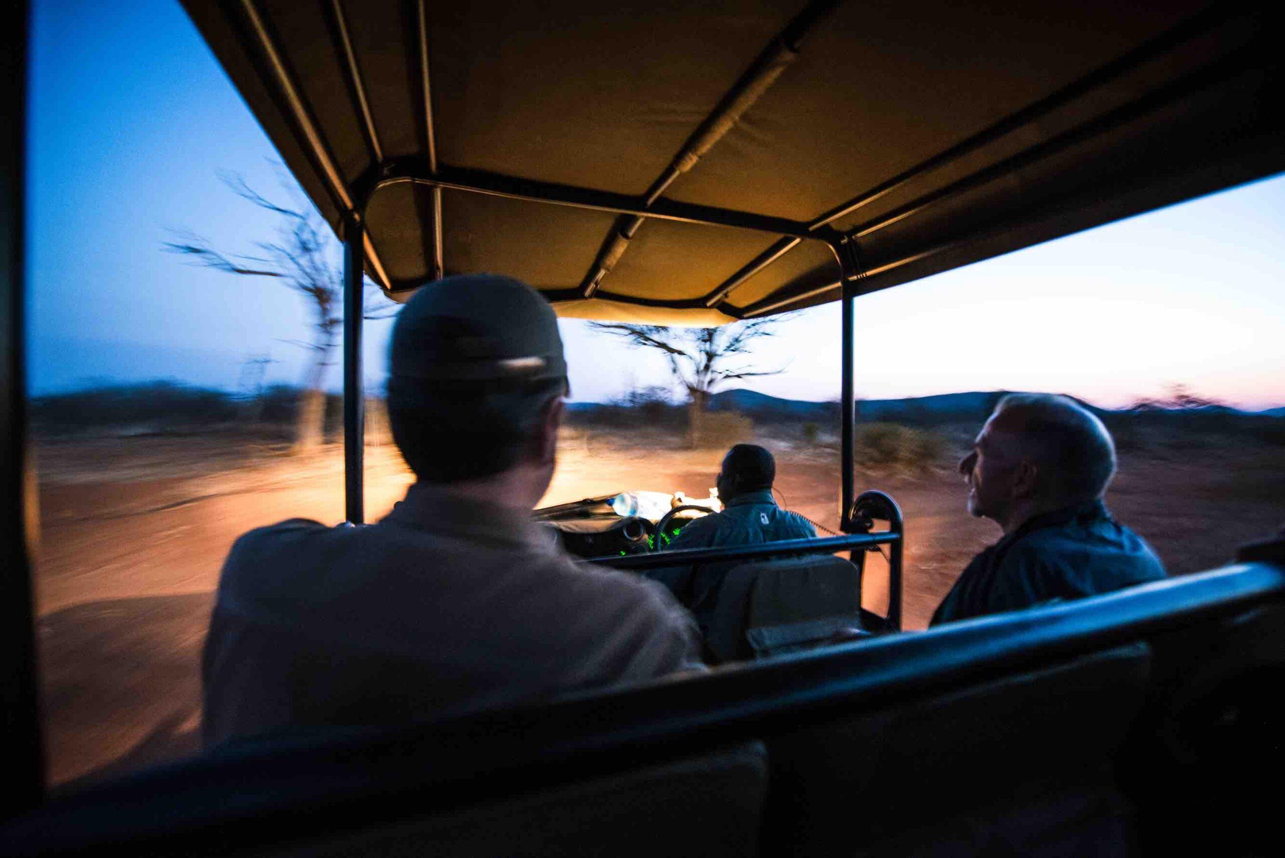 Zugreise mit Rovos Rail in Afrika. Von der Rückbank eines Safari Jeep sieht man zwei Gäste sowie den Ranger des Game Reserve. Draussen ist es bereits am Eindunkeln