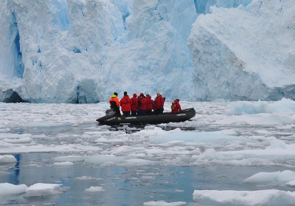 Reise in der Antarktis. In einem kleinen motorisierten Boot ist eine Expeditionsgruppe, umgeben von aufragenden Eisbergen und Eisschollen.
