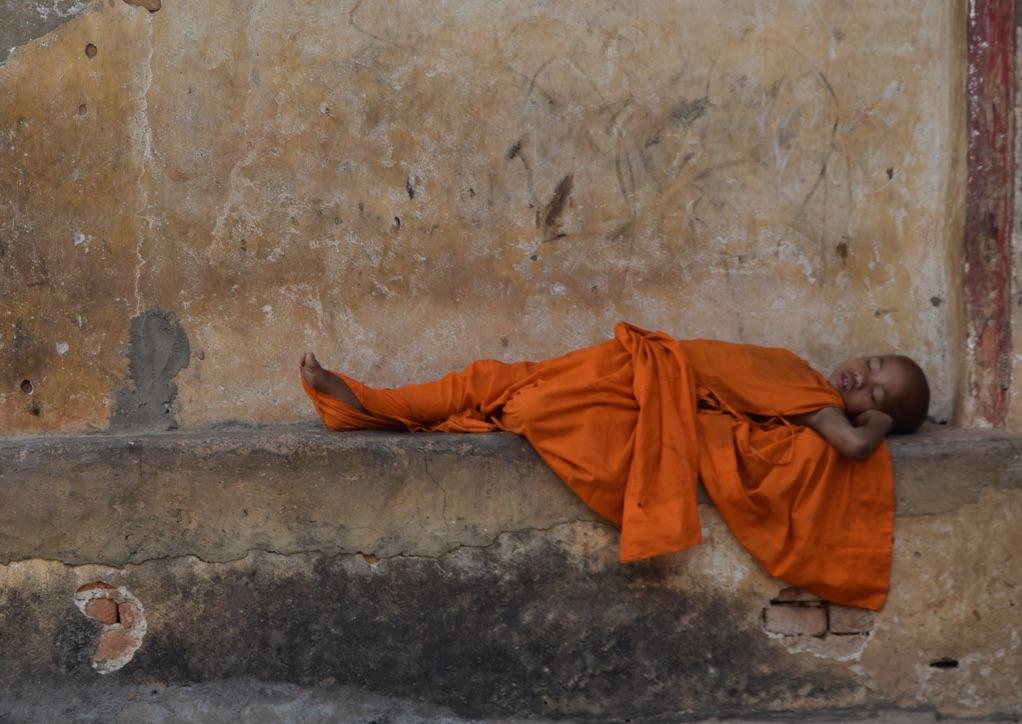 Reise in Myanmar in Asien. Junger buddhistischer Mönch mit orangefarbenem Ordensgewand schläft auf einer Steinbank