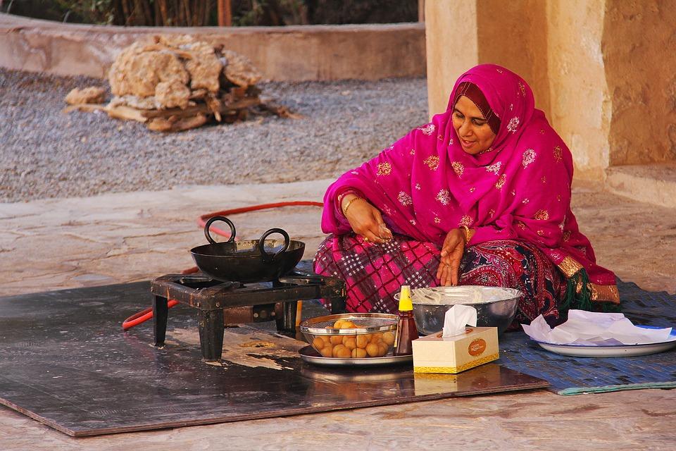 Reise in Oman im Orient. Einheimische Frau in traditioneller Kleidung sitzt auf dem Boden und frittiert Teigbällchen.