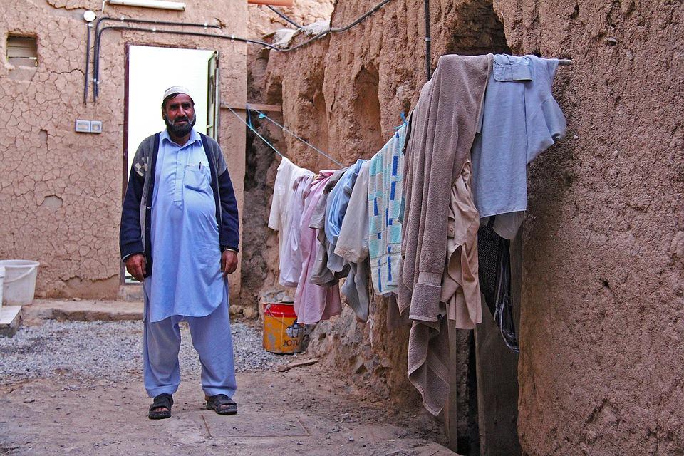 Reise in Oman im Orient. Einheimischer Mann in traditioneller Kleidung steht in einer schmalen Gasse, links von ihm hängt aufgehängte Wäsche.