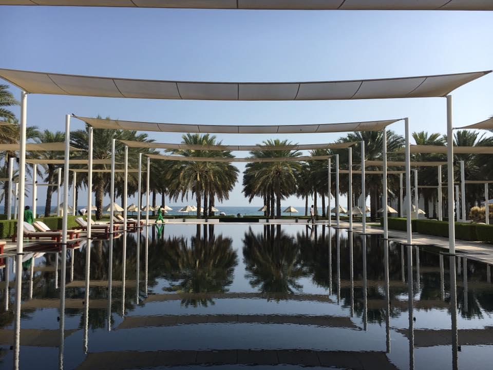 Reise in Oman im Orient. Der grosse Pool des  Al Bustan Palace in Maskat ist von Palmen und Liegestühlen umsäumt und mit Segeltuch Dach geschützt und liegt direkt am Meer.