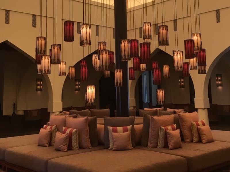 Reise in Oman im Orient. Eine gemütliche Sitzgruppe mit vielen Kissen unter typisch orientalischen Lampen im Chedi Resort in Maskat.