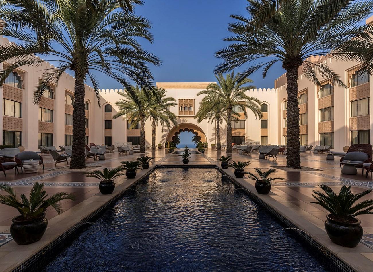 Reise in Oman im Orient. Grosszügiger Pool von Palmen umsäumt im orientalischen Shangri La Resort in Maskat.