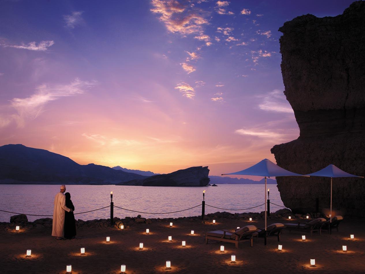 Reise in Oman im Orient. Der Strand vom Shangri La Resort und Spa in Maskat wird von zahlreichen Lämpchen beleuchtet, ein Paar bewundert den Sonnenuntergang.
