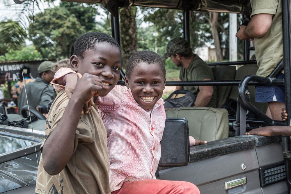 Reise im Kongo in Afrika. Einheimische Jungen sitzen auf der Kühlerhaube eines Jeep und lachen in die Kamera.