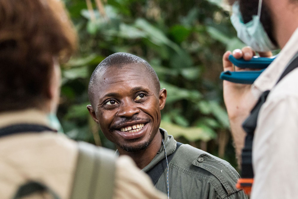 Reise im Kongo in Afrika. Ein einheimischer Guide ist im Urwald auf Safari mit einer Gruppe unterwegs und lacht freundlich in die Kamera.