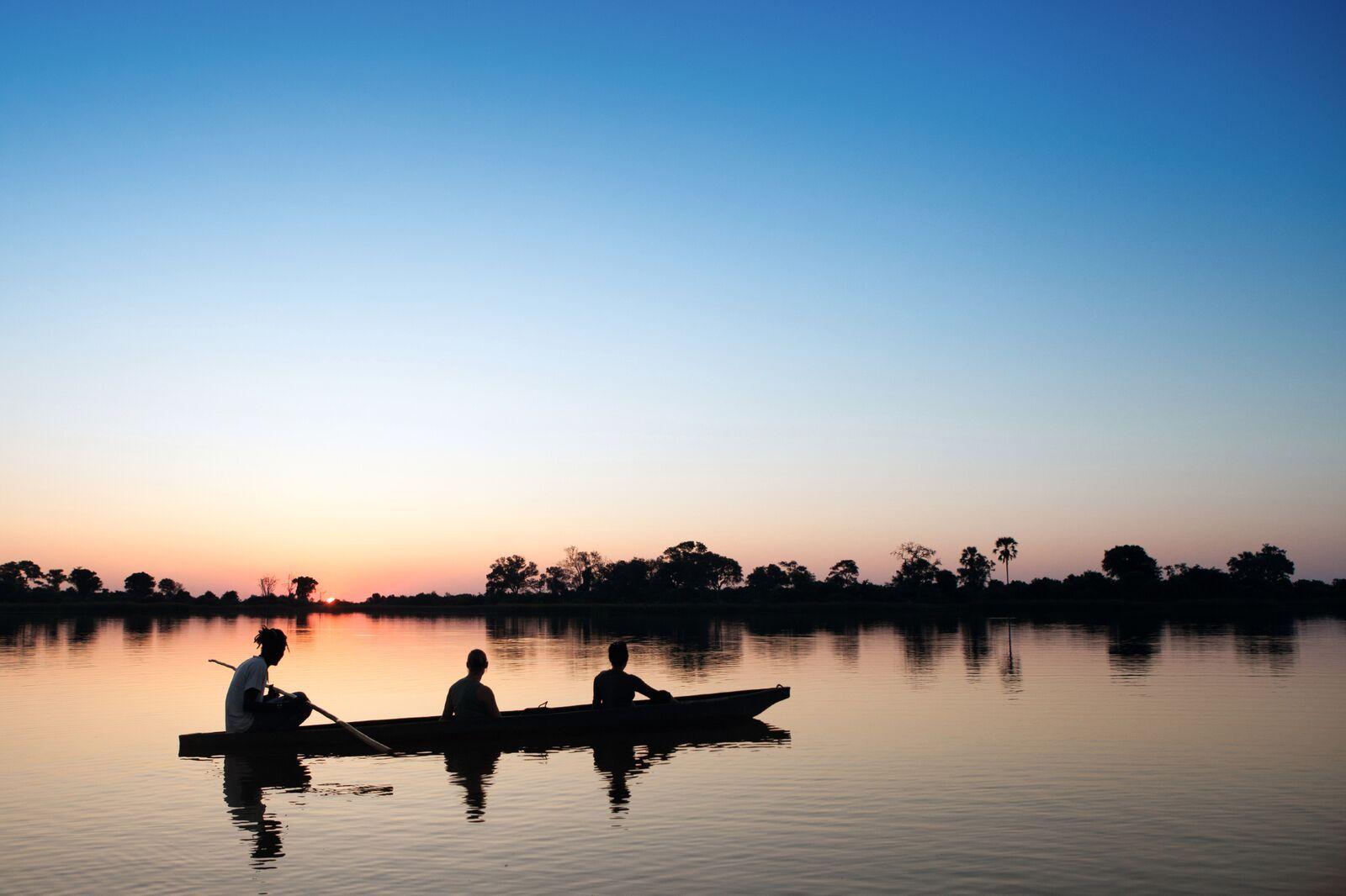 Reise in Sambia in Afrika. Stimmungsbild mit einem Kanu, in dem drei Personen sitzen und kurz nach Sonnenuntergang auf dem Fluss fahren.