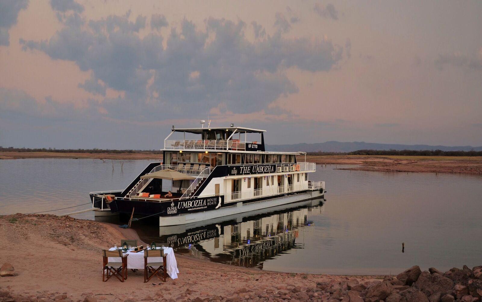 Reise in Sambia in Afrika. Ein Hausboot hat an einer Küste angelegt, am Strand steht ein Tisch, der für vier Personen gedeckt wurde.